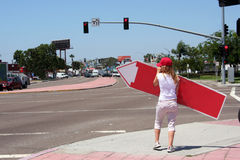 Back of Sign Twirling Girl. Cute blonde with baseball cap twirls a directional advertisement sign on a street corner. Image shows her back. This is a new way of Royalty Free Stock Photography