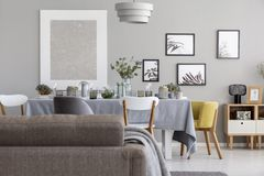 Back of a sofa and dining table with tableware, and graphics on a wall in a daily room interior. Real photo stock photography