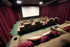 Back of soft couches with pillows in small hall of cinema. Stock Photo