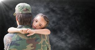 Back of soldier with daughter against black grunge background with flare stock photo