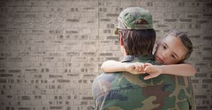 Back of soldier with daughter against brown brick wall royalty free stock photo