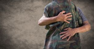 Back of soldier hugging against brown background with grunge overlay stock photography