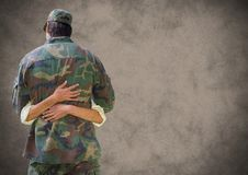 Back of soldier hugging with grunge overlay against brown background stock images