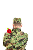 Back of a soldier with red rose over shoulder Royalty Free Stock Images