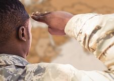 Back of soldier saluting against blurry brown map Stock Photography