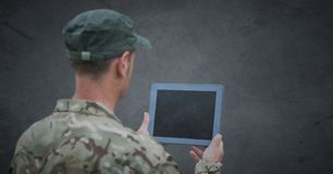 Back of soldier with tablet against grey background with grunge overlay royalty free stock photography