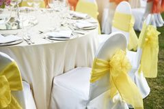 Back of spandex white cover chairs yellow organza sash for wedding reception dinner table stock images