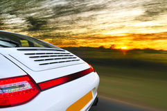 Back of speeding car. Details of the back of a speeding white car with motion blur. Sunset background Stock Image