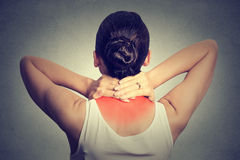 Back and spine disease. Back view of tired female massaging her painful neck Stock Photo