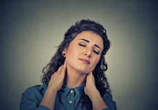 Back and spine disease. Tired woman massaging her painful neck Stock Image