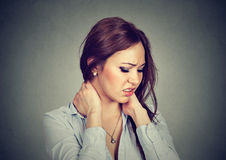 Back and spine disease. Tired woman massaging painful neck Stock Photo