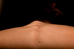 Back spine woman. The back, spine and shoulders of a girl bending forward on a black background Stock Images