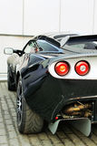 Back of sport car. Back of black sport car with red backlight on road Stock Photo