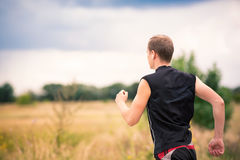 Back of sportive young man jogging outdoor. Back of sportive man runner jogging at great speed on a road stock photo