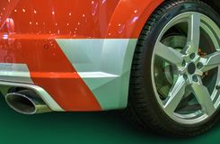 The back of the sporty luxury car concept car wheel bumper and silencer. Wheel with titanium disc and a racing tire and the rear bumper section and trunk of a Royalty Free Stock Photo