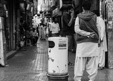 Back of standing man near dustbin. Dubai, UAE: a man standing near dustbin in a street of Deira Royalty Free Stock Photos