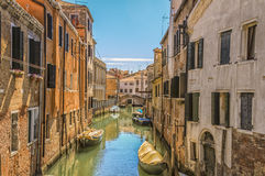 Back street canal in Venice. There are many canals and small bridges in Venice, Italy.  This scene makes one wonder about access to some parked boats.  Dorsoduro Stock Image