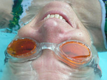 Back Stroke. Submerged woman swimming on her back in orange goggles Stock Image