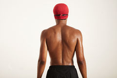 Back of a strong black swimmer in cap and goggles stock photography