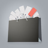 Back strong paper shopping bag with lot of tags on gray background. Back strong paper shopping bag with tag Stock Photo