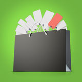Back strong paper shopping bag with lot of tags on green background. Back strong paper shopping bag with tag Royalty Free Stock Image
