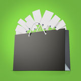 Back strong paper shopping bag with lot of tags on green background. Back strong paper shopping bag with tag Stock Photography