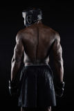 Back of strong young male boxer. On black background. Young african male in boxing gear stock image