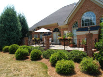 Back Terrace in Brick and Iron. Large brick patio with an iron railing on the back of an expensive home with arched windows. Well-kept planters and a covered Royalty Free Stock Images