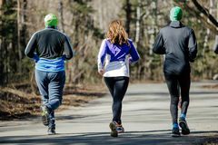 Back three runners. Running asphalt road in spring city Royalty Free Stock Images