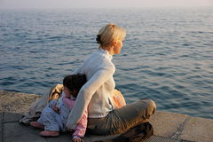 Back to back. Mother and child leaning against each other's back in front of the sea Stock Photo