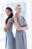 Back to back businesswomen looking at the camera Stock Images