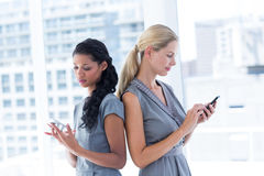 Back to back businesswomen texting messages. In the office Stock Photo