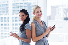 Back to back businesswomen texting messages Stock Image