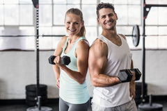 Back to back couple exercising with dumbbells Royalty Free Stock Photos