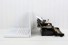 Back to Back Technology. Closeup of a white desk with a modern laptop computer and an antique typewriter back to back. Horizontal format with copy space. Old vs Stock Photography