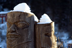 Back to back totem poles with snow on top Royalty Free Stock Photography
