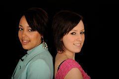 Back to back women. Head and shoulder horizontal portrait of two smiling woman of diverse backgrounds standing back to back, isolated on a black background Stock Photo
