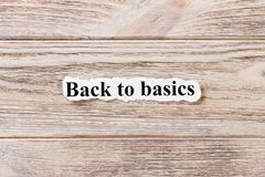 Back to Basics of the word on paper. concept. Words of Back to Basics on a wooden background.  royalty free stock images