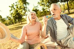 Happy elderly man blowing soap bubbles. Back to childhood. Happy nice elderly men sitting together with his wife and blowing soap bubbles while having fun Royalty Free Stock Images