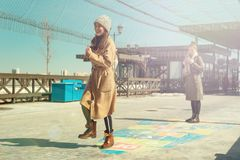 Back to childhood. Two women jumping on the pavement playing hopscotch stock photos