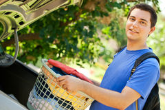 Back to college. College student putting his laundry in the trunk of his car going back to school Stock Photography