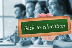 Back to education against smiling friends students talking and writing. The word back to education and hand showing chalkboard against smiling friends students Royalty Free Stock Images