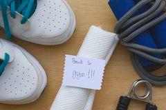 Back to gym. Message written on a piece of paper: Back to gym. Sport items background: snickers,jumping rope,white towel, hand gripper Royalty Free Stock Image