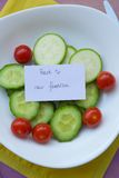 Back to raw foodism. Message on the plate with raw vegetables: Back to raw foodism. Food background: fork,knife,cucumbers,cherry tomatoes,raw zucchini. The plate Stock Photo