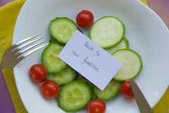 Back to raw foodism. Message on the plate with raw vegetables: Back to raw foodism Food background: fork,knife,cucumbers,cherry tomatoes,raw zucchini. The plate Royalty Free Stock Photo