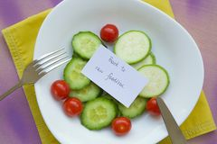 Back to raw foodism. Message on the plate with raw vegetables: Back to raw foodism. Food background: fork,knife,cucumbers,cherry tomatoes,raw zucchini. The plate Royalty Free Stock Photo