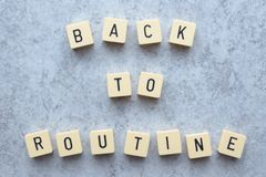 Back to routine text Game tiles on grey flecked stone background. Back to routine message text formed by game tiles and placed on a grey flecked stone background stock photography