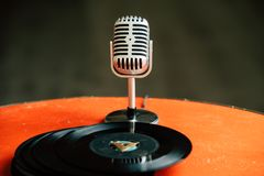 Back to 50s - nostalgic image of a 50`s microphone standing on an old orange table with old vinyl records. Nostalgic image of a 50`s microphone standing on an royalty free stock photo
