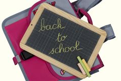 Back to school. School bag and chalk board isolated on white stock photography