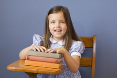 Back to School. Little girl sitting at a wooden school desk Stock Photography